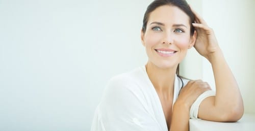 Woman leaning on left elbow looking forward
