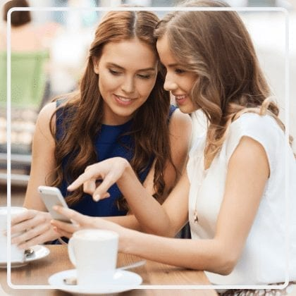 Two women looking at phone - New Image Med Spa